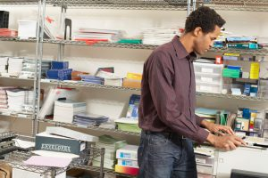 Male office worker standing by storage shelving, using fax machine